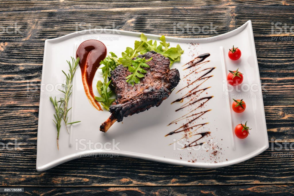 Steak on a bone with tomatoes and a hazelnut. Steak Fiorentino. On a wooden background. Free space for your text. Top view. stock photo