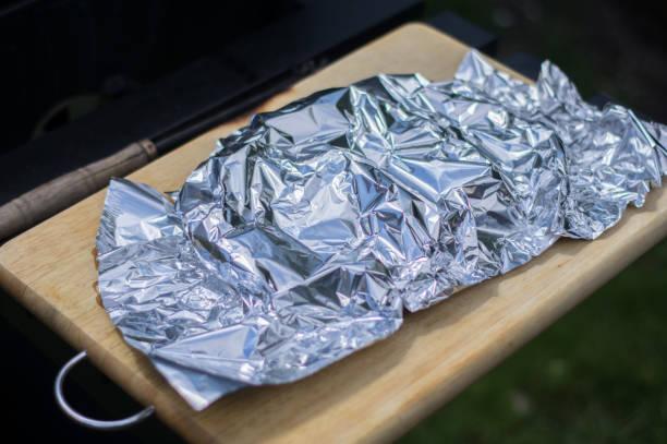 salmon wrapped in tin foil on wood cutting board