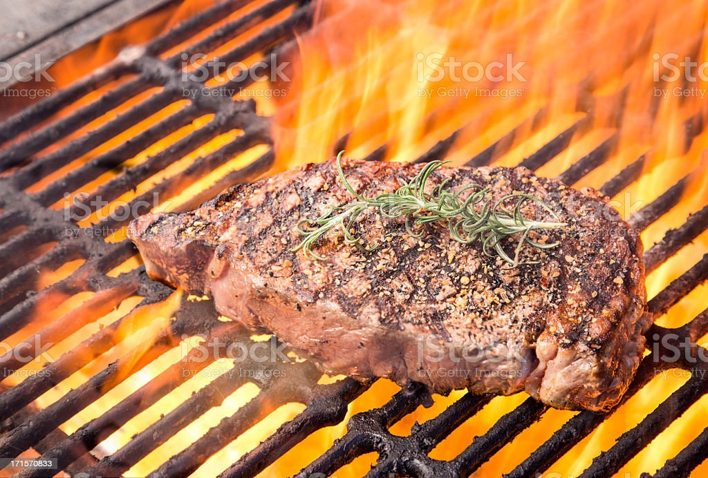 Steak on Grill with Flames stock photo