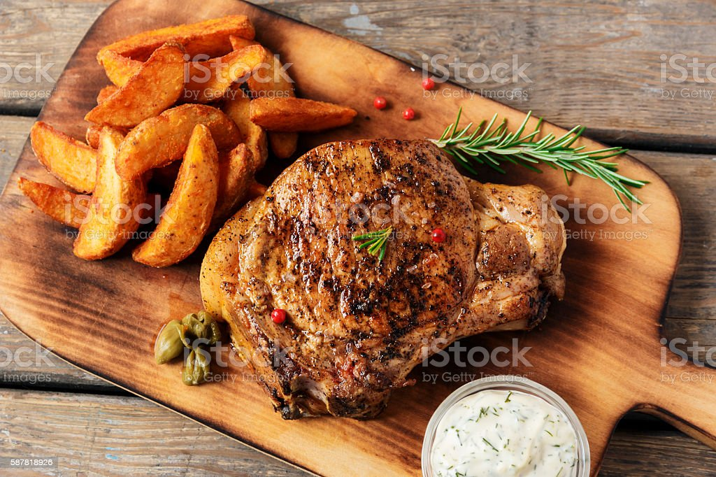 steak on the bone steak with baked potato and gravy stock photo