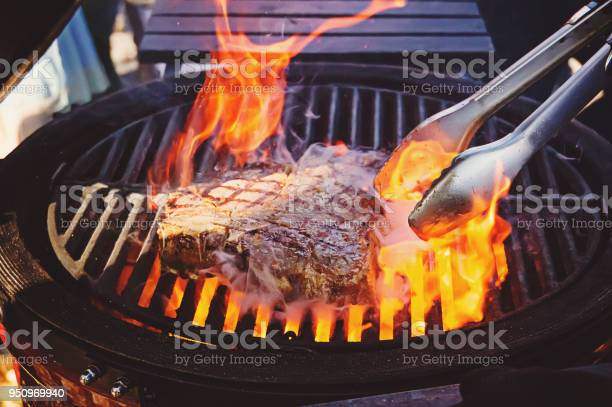 Photo of Steak on the grill with flames