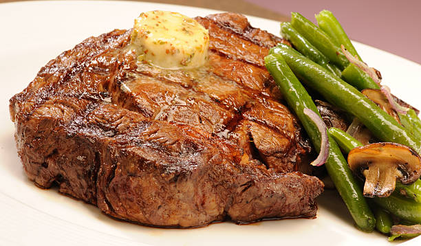 Steak A hot juicy Rib-eye steak green beans and muchrooms rib eye steak stock pictures, royalty-free photos & images