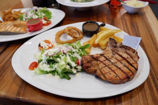 steak-schweinekoteletts - gegrilltes schweinekoteletts stock-fotos und bilder