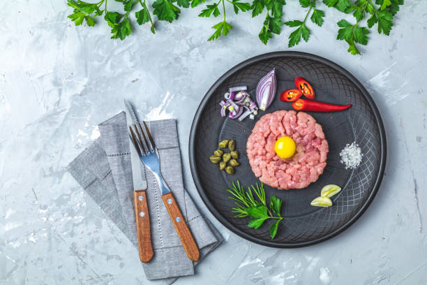 Steak tartare with yolk and ingredients on black ceramic plate stock photo
