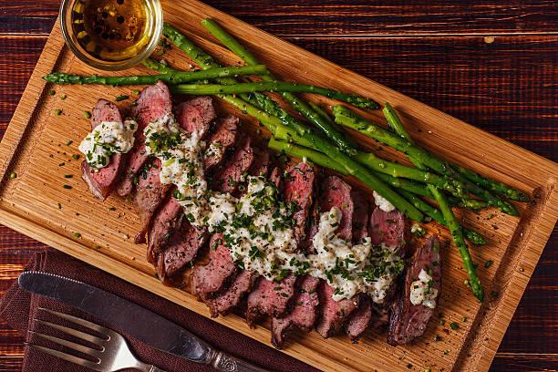 steak mit blauschimmelkäse-sauce, serviert mit spargel. - steak anbraten stock-fotos und bilder