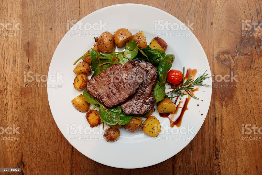 Steak with fried potatoes on wooden table stock photo