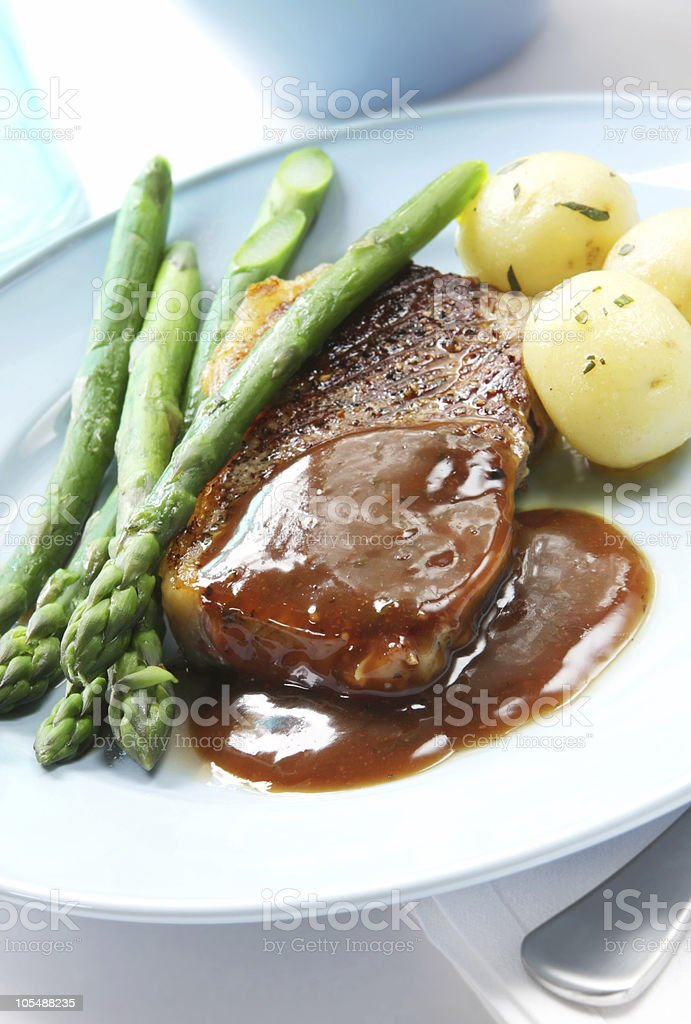 Steak with gravy, asparagus and potatoes royalty-free stock photo