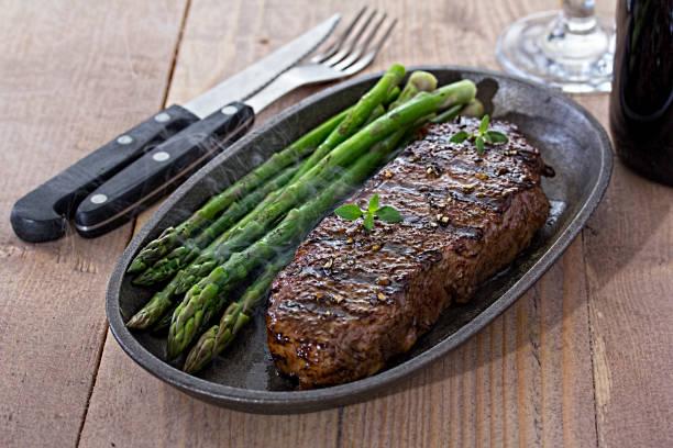 steak mit grünem spargel - steak anbraten stock-fotos und bilder