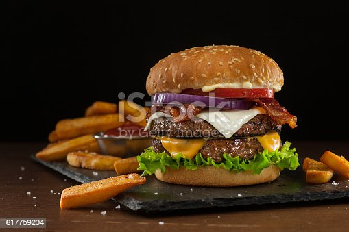 High resolution digital capture of a steakhouse-style double bacon cheeseburger with steak fries. This cheeseburger is made with two patties of ground steak, Cheddar and Monterey Jack cheeses, crispy bacon slices, fresh tomatoes, lettuce, and onion, all on a sesame seed bun. A ramekin of ketchup is visible amongst the fries. Background is dark and atmospheric, with room to expand and place copy.