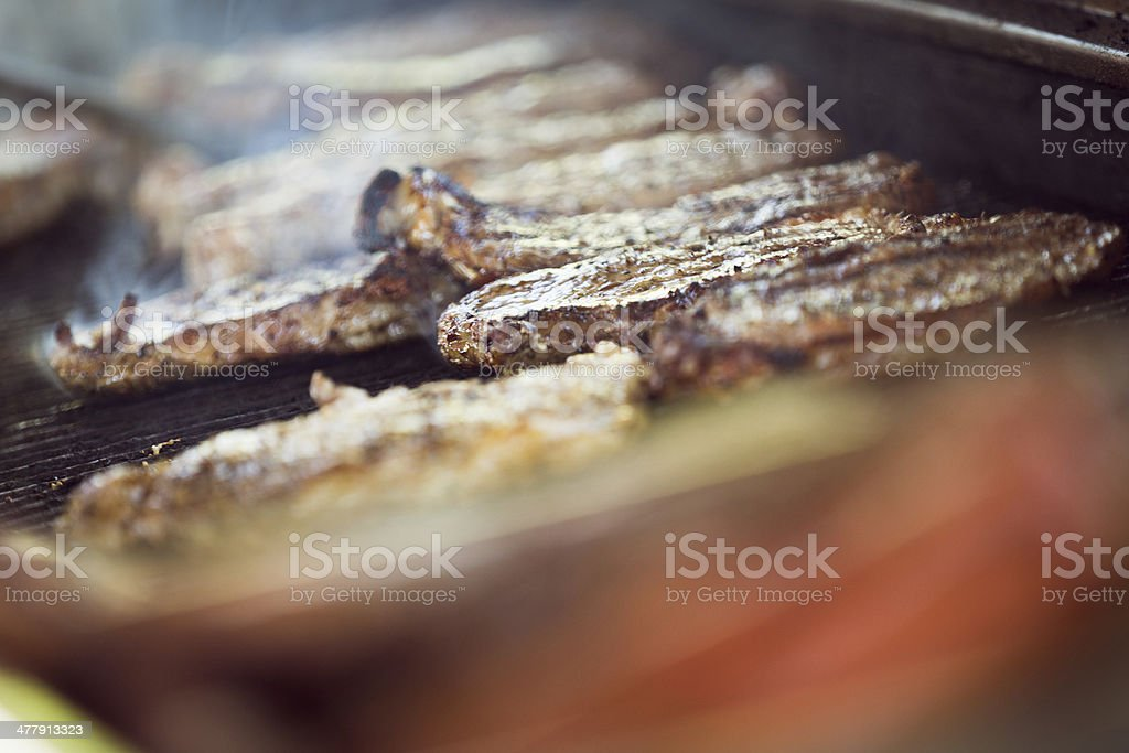 Steaks being cooked on grill at outdoor cookout royalty-free stock photo