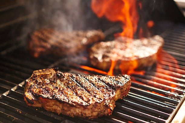 steaks cooking over flaming grill stock photo