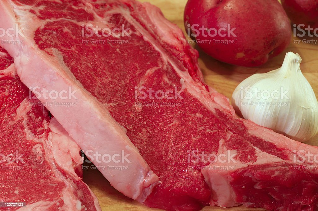 Steaks, potatoes, and garlic royalty-free stock photo