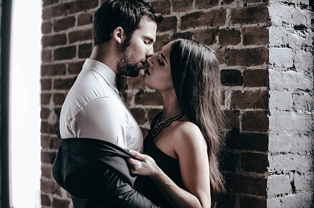 stealing a kiss. - man dominating woman stock photos and pictures