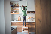 Young boy, home alone, trying to reach for something from a kitchen cabinet