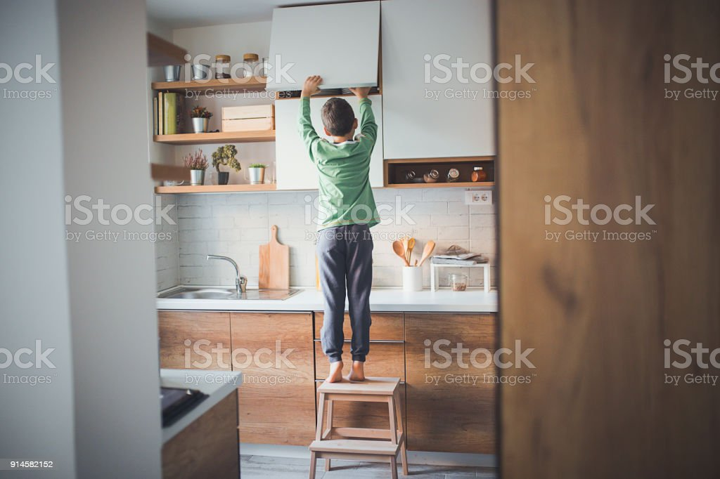 Stealing cookies from the kitchen cabinet stock photo