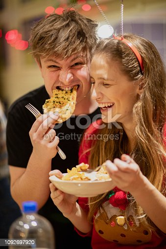 Young woman is eating at a house party and her friend has stolen a piece of garlic bread. He is looking at the camera while taking a bite.