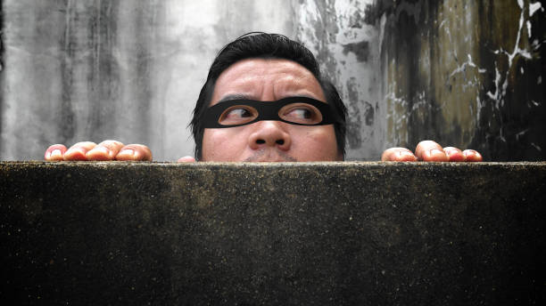 Stealing men with camouflage facial mask. Climbing the wall of the house to peep stock photo