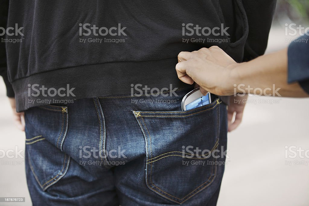 Stealing mobile phone from back pocket stock photo