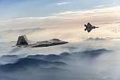 F-22 Stealth Jet Fighters flying over fogy mountains at sunset