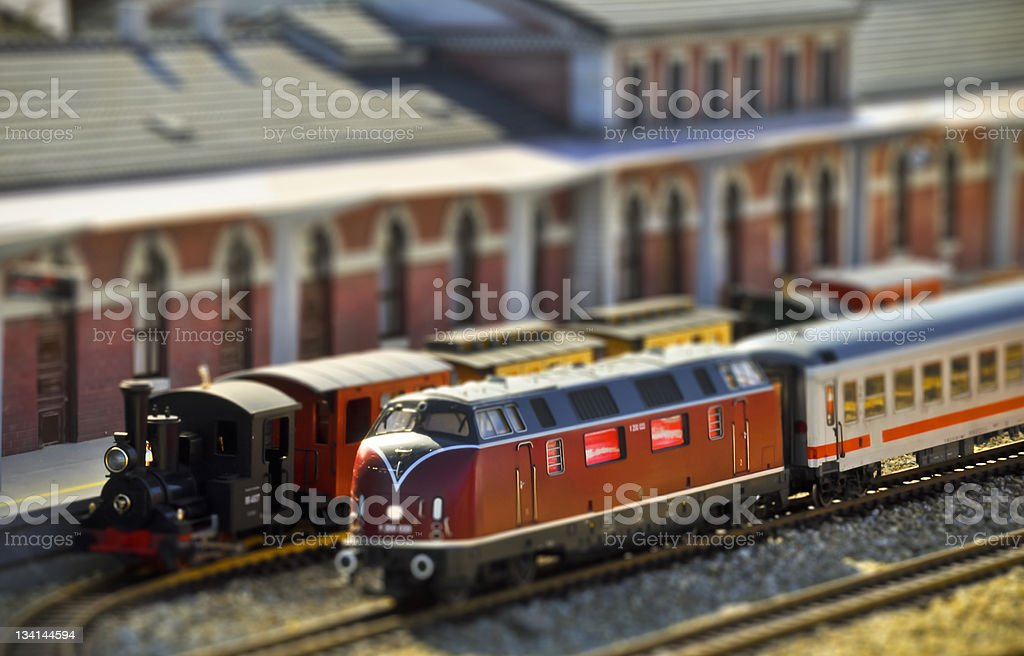 Steam and diesel trains on the railway station. Tilt shift stock photo