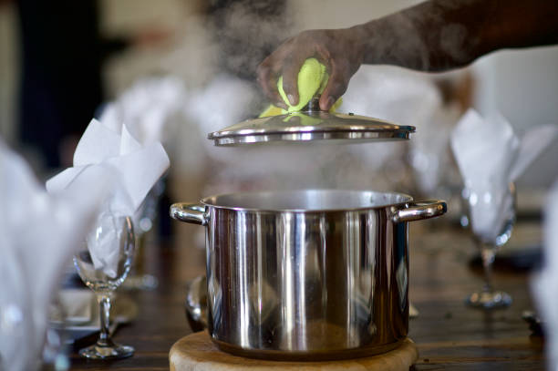 Steam as Lifting the metal pot lid stock photo