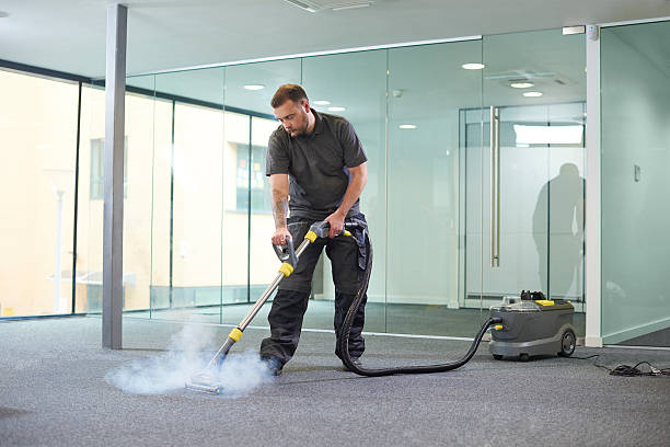 steam cleaning the office carpet a male cleaning contractor steam cleans an office carpet in a empty office in between tenants. cleaning equipment stock pictures, royalty-free photos & images