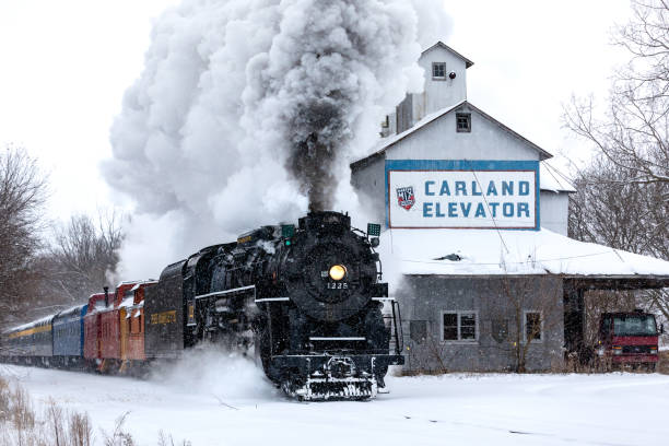 CARLAND, MICHIGAN,USA-DECEMBER 09: Steam engine Pere Marquette 1225 speeds by an abandoned grain elevator on December 9, 2017. This steam engine is known as the North Pole Express and travels between the towns of Owosso and Ashley