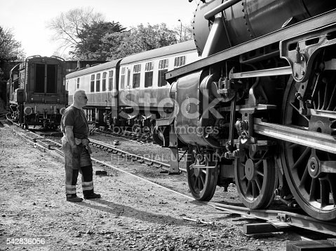Sheringham, Norfolk, England - May 5, 2016: An engineer overseeing the difficult process of transferring a steam engine from the back of a flatbed lorry to the existing railway track, where it will be collected by a diesel shunting engine. The steam engine is number 45337 of the LMS Stanier Class) being delivered to Sheringham station from where the North Norfolk Railway - a heritage line - operates. Sheringham is a coastal town in Norfolk, eastern England, and the line runs on former M&GN Railway tracks between Sheringham and Holt. The North Norfolk Railway operates a variety of engines and carriages, both steam and diesel. The photograph was taken in the public car park behind the station.