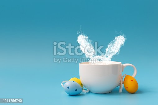 istock Steam in rabbit ears shape from coffee cup decorated Easter colored eggs. Morning drink. Easter celebration concept. Copy space 1211756740