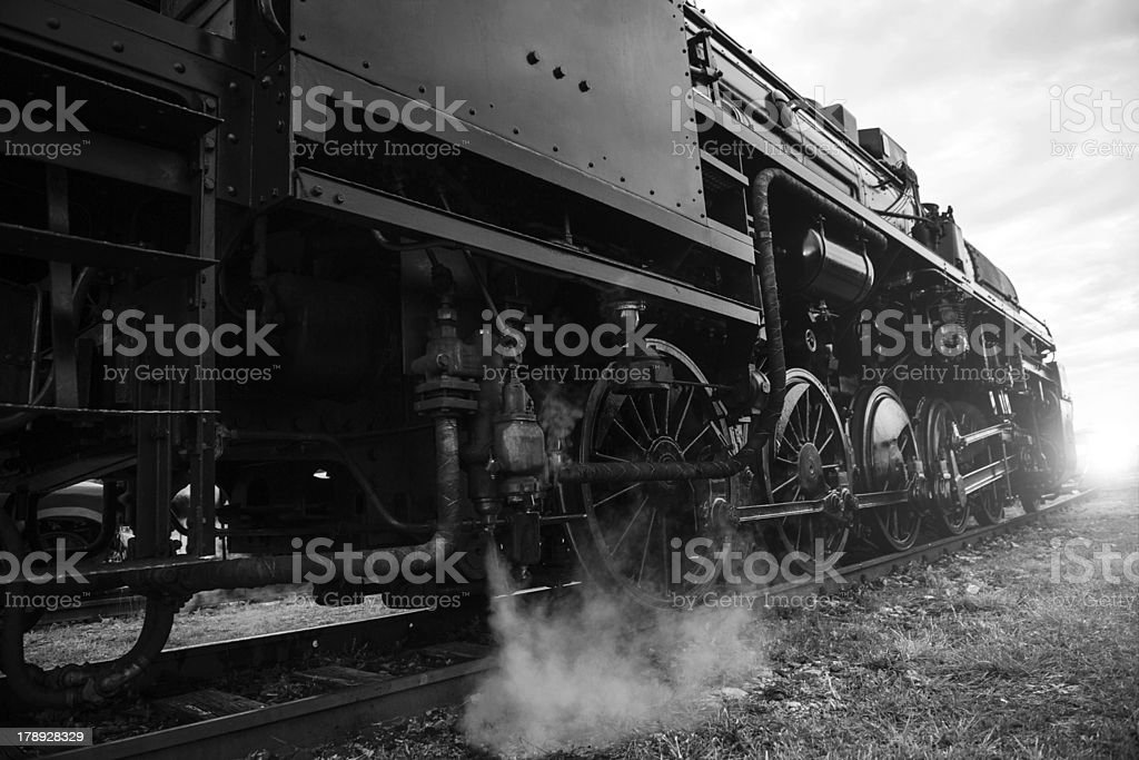 steam locomotive heading towards sunset stock photo