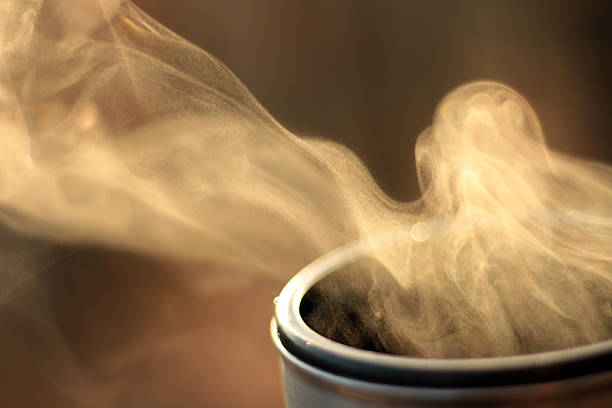 Steam of hot tea against sun in nature, Evaporation Steam of hot tea in a close-up against the sunlight; Copy space; Shallow depth of field evaporation stock pictures, royalty-free photos & images