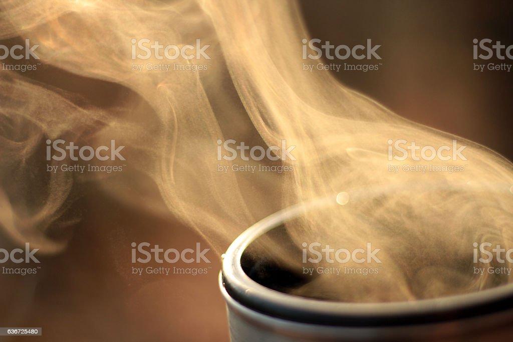 Steam of hot tea against sun in nature, Evaporation
