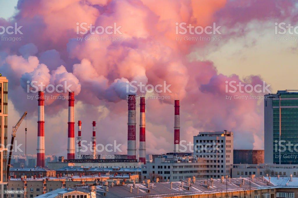 Ånga eller rök kommer från rören. Kombinerad värme- och kraftverk i staden. Landskap i solnedgång eller dawn - Royaltyfri Avgaser Bildbanksbilder