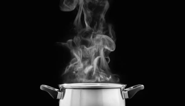 Dampf über Kochtopf in der Küche auf dunklem Hintergrund – Foto
