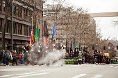 Leading the Seattle Firefighters Pipes and Drums at the Seattle St. Patrick's Day parade, are a group of men covered in steam, coming from the ground, on March 17, 2018.