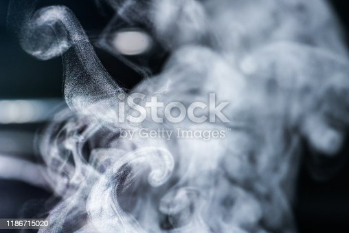 Close up - abstract shoot of vaporizing steam in the air on black background. Good for illustration of vaporizing, boiling tea, hot drinks or smoking electronic cigarette