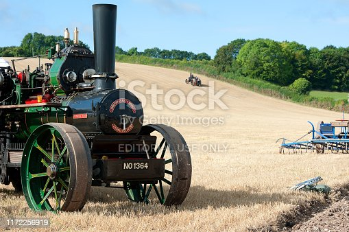 Ploughing steam traction engines prepare to pull plough, Tarrant Hinton, Dorset, England, UK. Steam driven ploughing engines are also road locomotives for hauling loads and generating power for rides and lighting. Traction engines originally designed for heavy haulage on public roads, were larger than normal traction engines and with three-speed gearing and extra water tank under the boiler for greater distances between water stops. Ploughing was achieved by pulling a plough by steel cable between two engines at opposite ends of any field