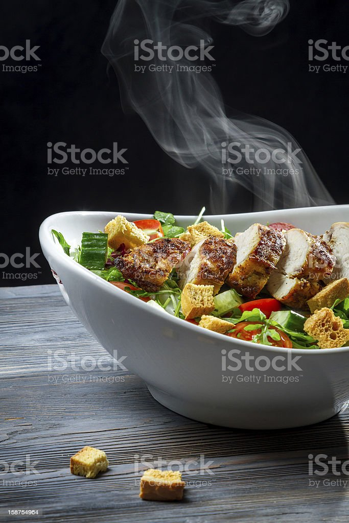 Steam rising from a freshly roasted chicken on salad royalty-free stock photo