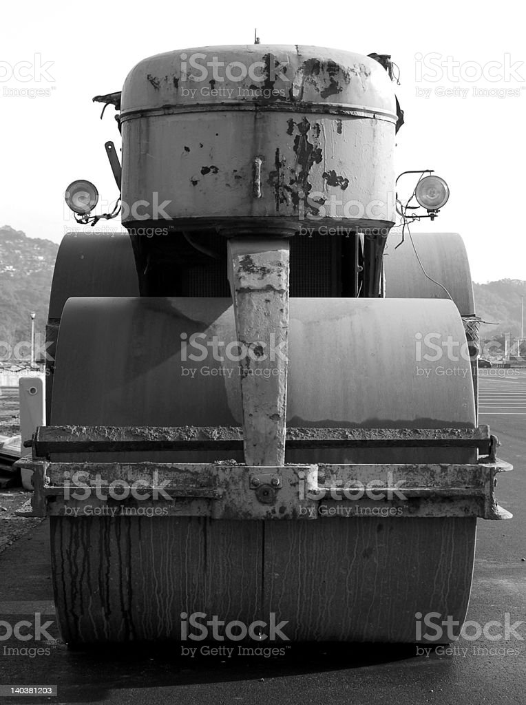A black and white image of a steam roller with a somewhat...