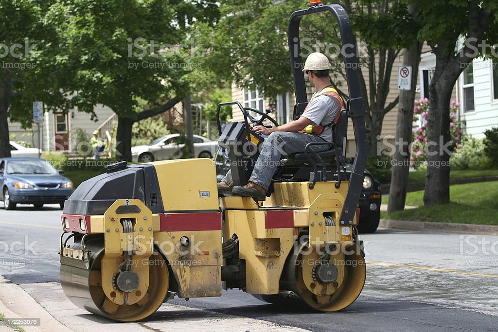 Steam roller and its operator smooth out freshly laid asphalt on a...