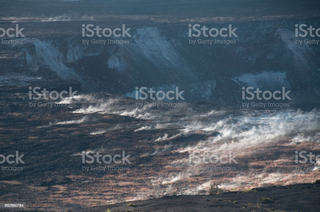 Steam seeps out of the ground in a volcanic crater. stock photo