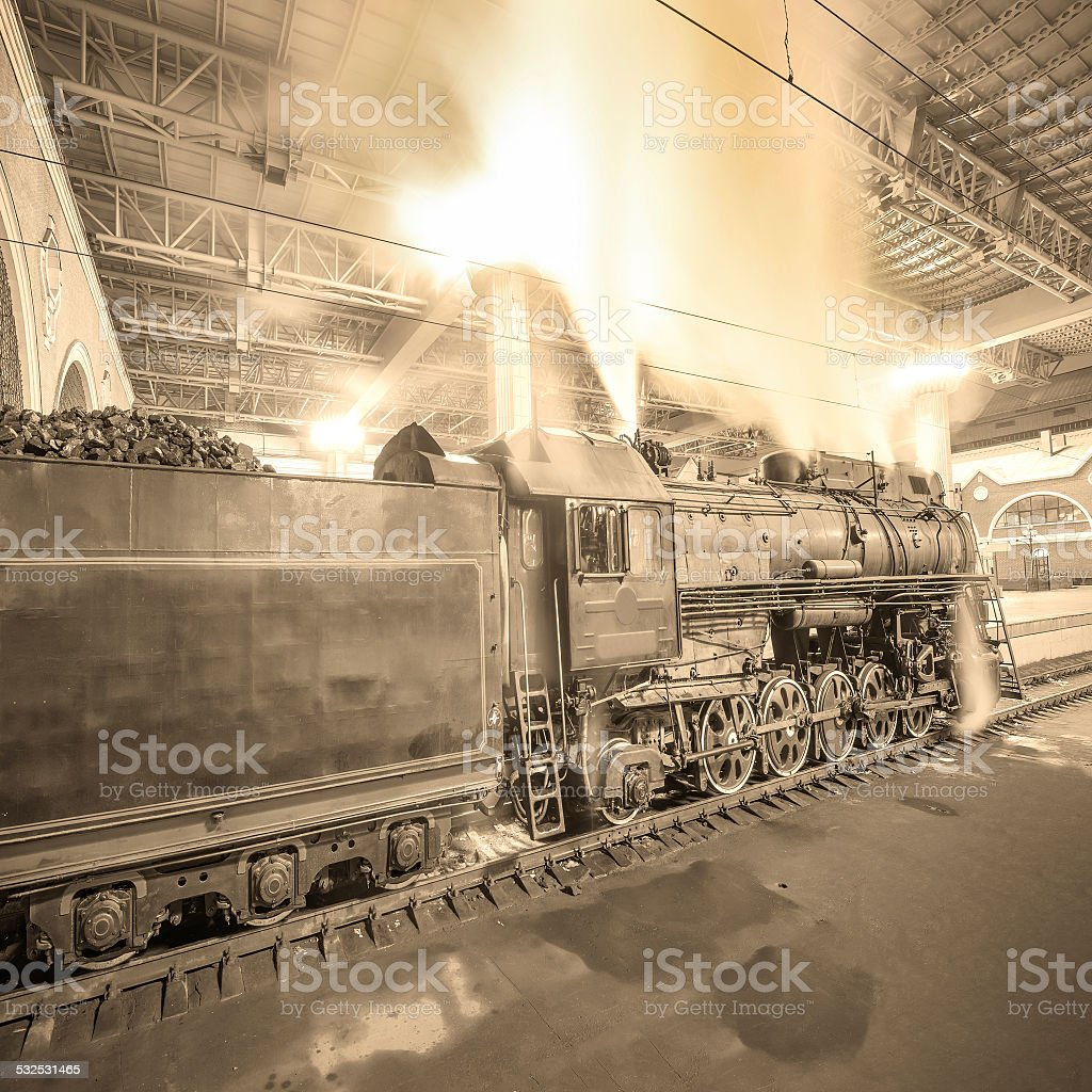 Steam train arrives to the station at night time. stock photo