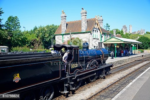 Corfe, United Kingdom - July 19, 2016: LSWR T9 Class 4-4-0 steam train entering the railway station with the castle to the rear and people going about their business, Corfe, Dorset, England, UK, Western Europe.