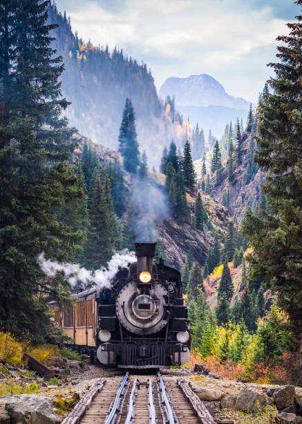dampfzug überqueren einer trestle-brücke in den bergen - lokomotive stock-fotos und bilder