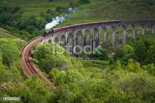 White smoke puffing evocatively from a historic steam train thundering across the iconic arches of the Glenfinnan Viaduct over a green mountain glen deep in the Highlands of Scotland, UK. ProPhoto RGB profile for maximum color fidelity and gamut.