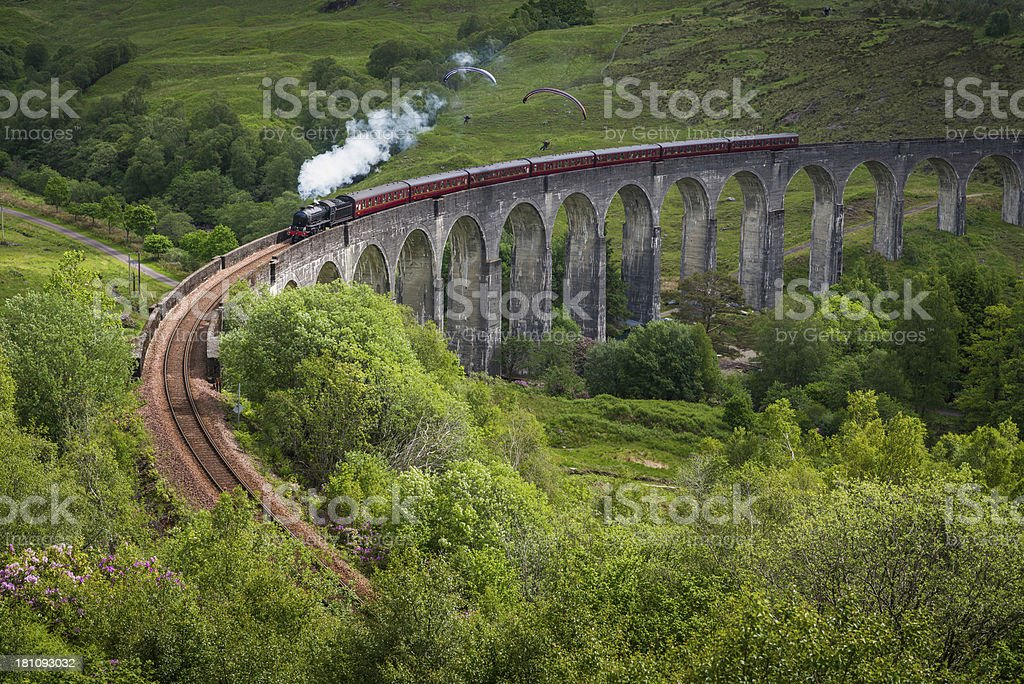 Steam train crossing viaduct over Highland mountain glen Scotland stock photo