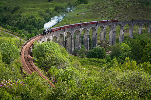 Steam train crossing viaduct over Highland mountain glen Scotland stock photo