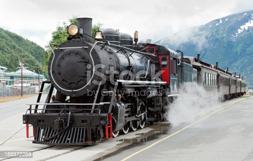 The White Pass steam train waiting in the train station sidings at the port of Skagway with a cruise ship in the background