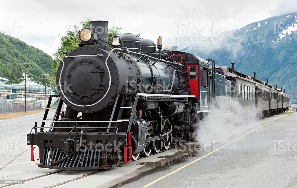 Steam train driving down tracks in Skagway, Alaska  stock photo