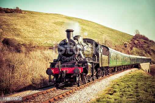istock Steam Train Gently Moving Through the English Countryside 1158772910